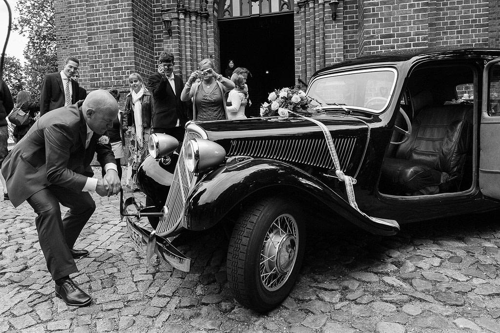 Bräutigam startet mit der Hamdkurbel den Motor vom Hochzeitsauto Citroen Gangsterlimosine CV 11 bei der Landhochzeit vor der Kirche in Röbel an der Müritz in Mecklenburg Vorpommern beim Hochzeitsfotograf Landhochzeit Hamburg