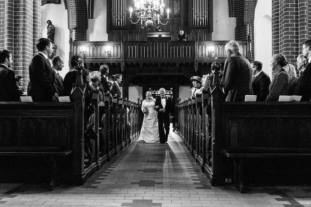 Brautvater führt die Braut beim Einzug in die Sankt Marien Kirche in Röbel an der Müritz in Mecklenburg Vorpommern beim Hochzeitsfotograf Landhochzeit Hamburg