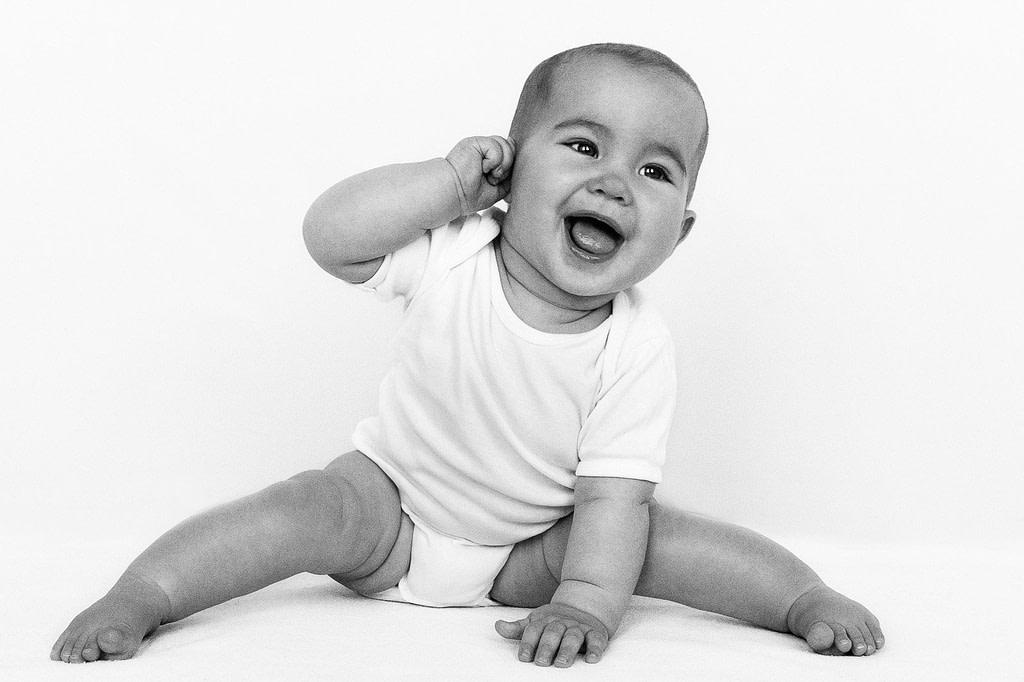 Baby sitzt auf dem Boden und zieht an seinem Ohr beim Baby Fotoshooting in Hamburg Eimsbüttel