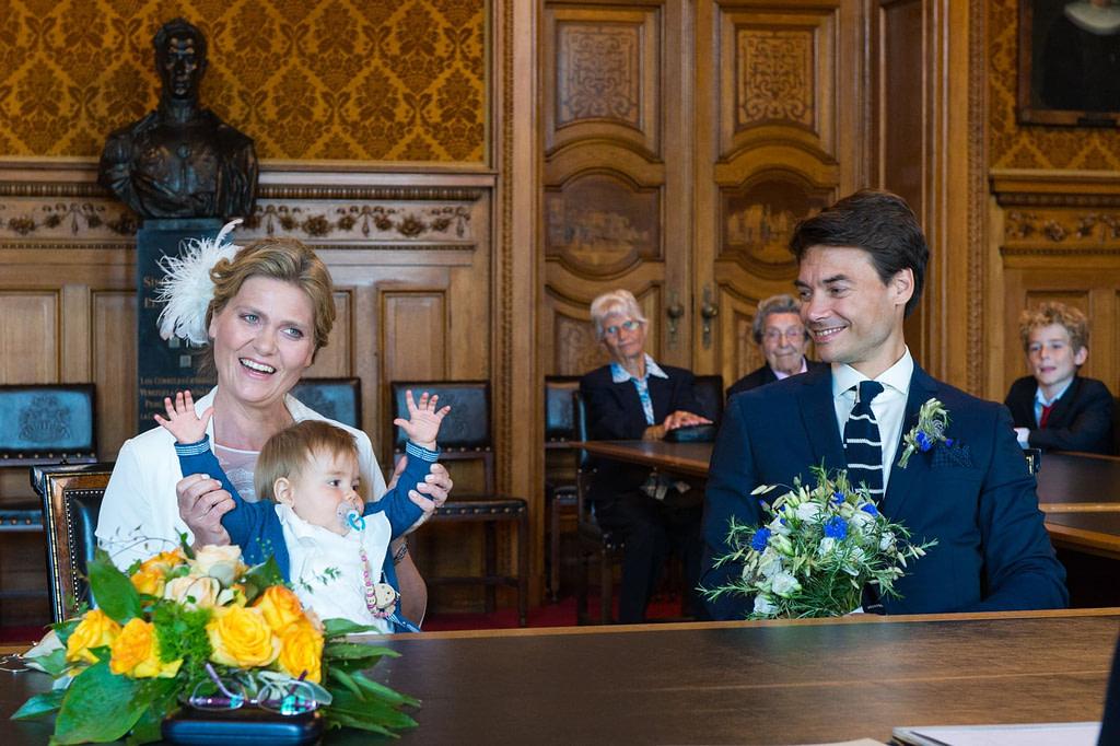 Das Hochzeitspaar mit Hochzeitskind lauscht der Rede der Standesbeamtin im Phönixsaal vom Hamburger Rathaus beim Hochzeitsfotograf Hamburg
