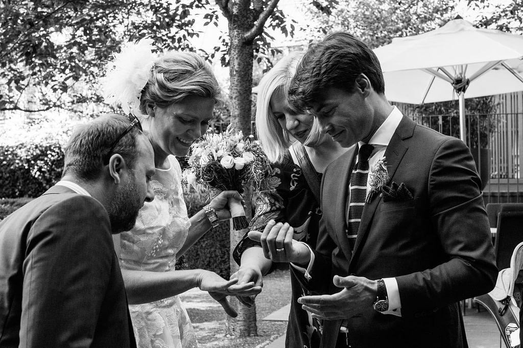 Braut, Bräutigam und Hochzeitsgäste begutachten die Hochzeitsringe beim Hochzeitsfotograf Hamburg
