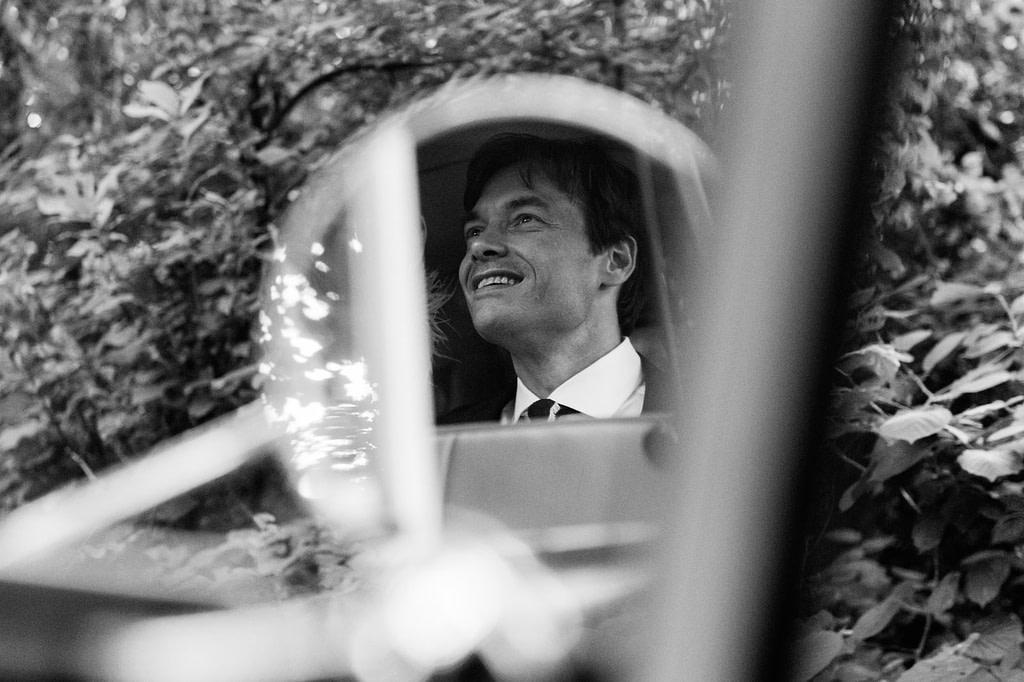 Der Bräutigam freut sich über eine Fahrt mit dem Hochzeitsauto VW Bulli T1 am Goldschätzchen der Koch Fabrik auf dem Golf Park Peiner Hof in Priesdorf beim Hochzeitsfotograf Hamburg