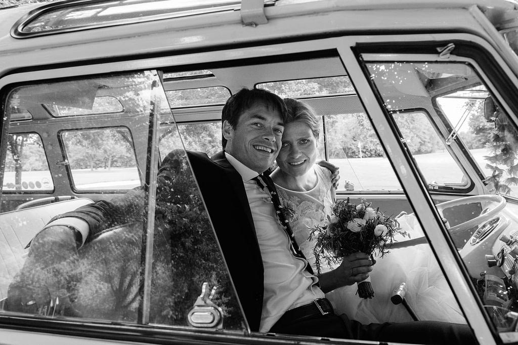 Braut und Bräutigam genießen eine Fahrt mit dem Hochzeitsauto VW Bus T1 am Goldschätzchen der Koch Fabrik auf dem Golf Park Peiner Hof in Priesdorf beim Hochzeitsfotograf Hamburg