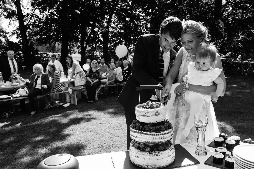 Das Hochzeitspaar schneidet gemeinsam die Hochzeitstorte an am Goldschätzchen der Koch Fabrik auf dem Golf Park Peiner Hof in Priesdorf beim Hochzeitsfotograf Hamburg