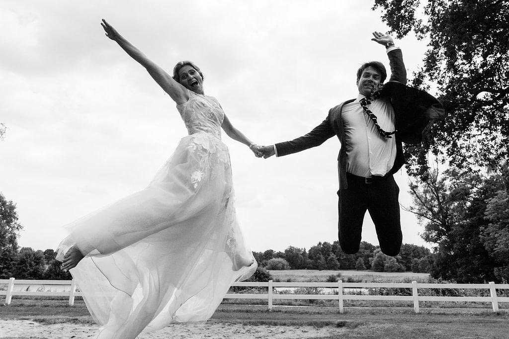 Das Hochzeitspaar springt vor Freude gemeinsam in die Luft am Goldschätzchen der Koch Fabrik auf dem Golf Park Peiner Hof in Priesdorf beim Hochzeitsfotograf Hamburg