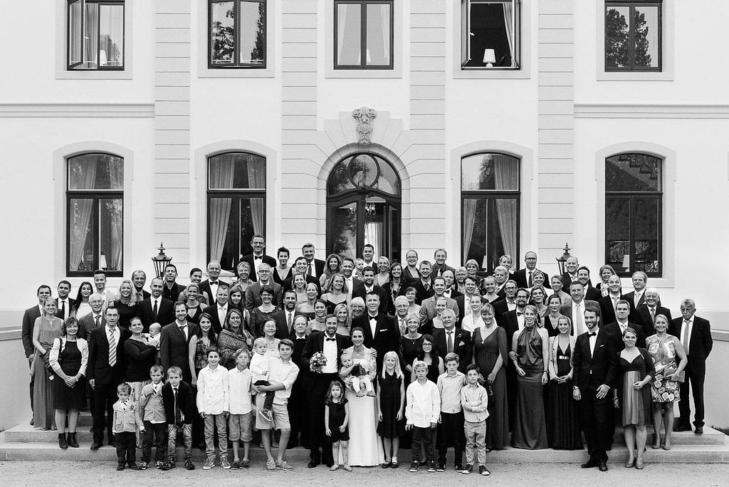 Gruppenfoto der Hochzeitsgesellschaft auf der Treppe zum Schloß Weissenhaus Grand Village Resort an der Ostsee beim Hochzeitsfotograf Hamburg
