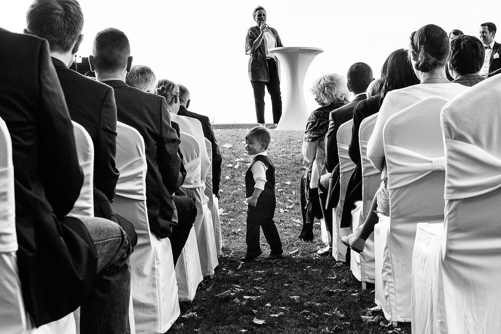 Kleiner Junge läuft bei der Traurede an den Hochzeitsgästen entlang an der Villa im Jachthafen bei Hochzeitsfotografie Hamburg