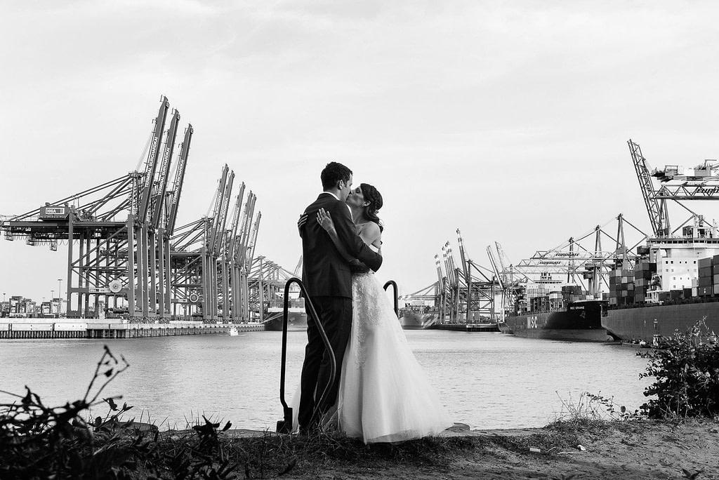 Hochzeitskuß im Parkhafen vor der Kulisse der Containerbrücken im Waltershofer Hafen bei Hochzeitsfotografie Hamburg