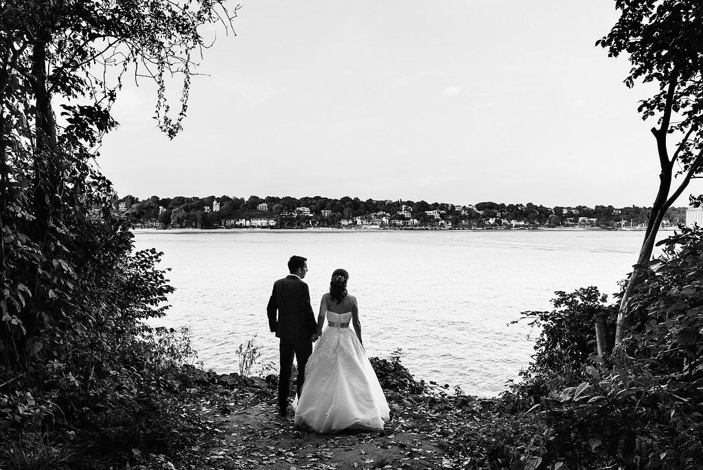 Das Hochzeitspaar genießt den Blick vom Bubendeyufer über die Elbe nach Övelgönne bei Hochzeitsfotografie Hamburg