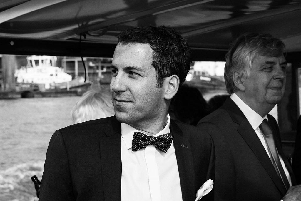 Bräutigam mit seinen Hochzeitsgästen auf der Barkasse auf dem Weg zur Villa im Jachthafen bei Hochzeitsfotografie Hamburg