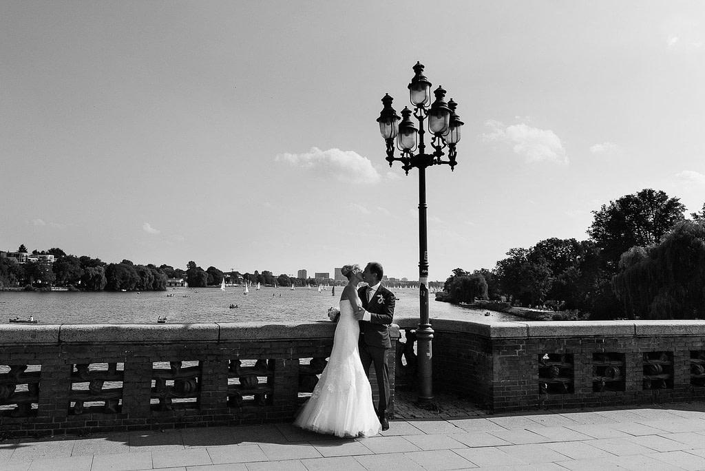 Ein Hochzeitskuß auf der Krugkoppelbrücke in Harvestehude mit Blick auf die Außenalster beim Hochzeitsfotograf Hamburg