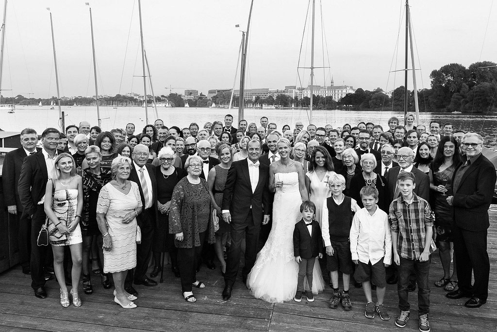 Gruppenbild der Hochzeitsgesellschaft auf dem Anleger vom Restaurante Portonovo mit Blick auf das Hotel Atlantic am Alsterufer auf der Außenalster am Rothenbaum beim Hochzeitsfotograf Hamburg