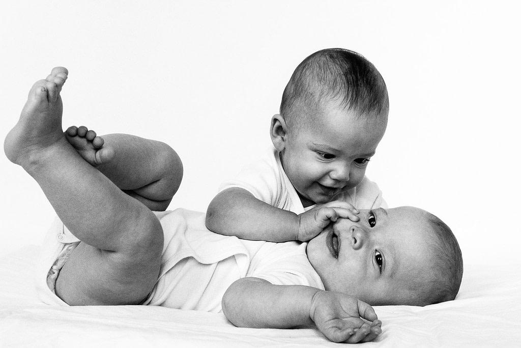 Zwillinge spielen miteinander auf der Decke beim Baby Fotoshooting in Hamburg Langenhorn