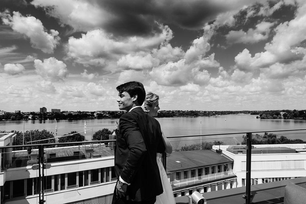 Das Hochzeitspaar genießt den Panorama Blick über die Aussenalster von der Dachtersse vom Hotel The George in Sankt Georg beim Hochzeitsfotograf Hamburg