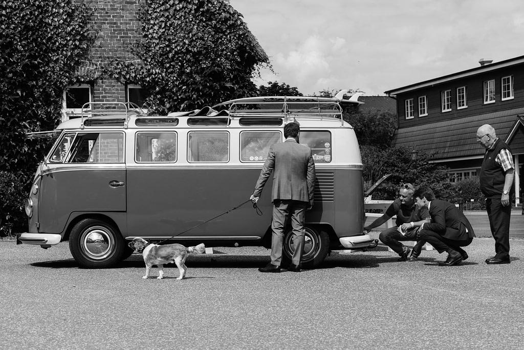 Das Hochzeitsauto VW Bus T1 wird vom Bräutigam und Gästen inspiziert am Goldschätzchen der Koch Fabrik auf dem Golf Park Peiner Hof in Priesdorf beim Hochzeitsfotograf Hamburg
