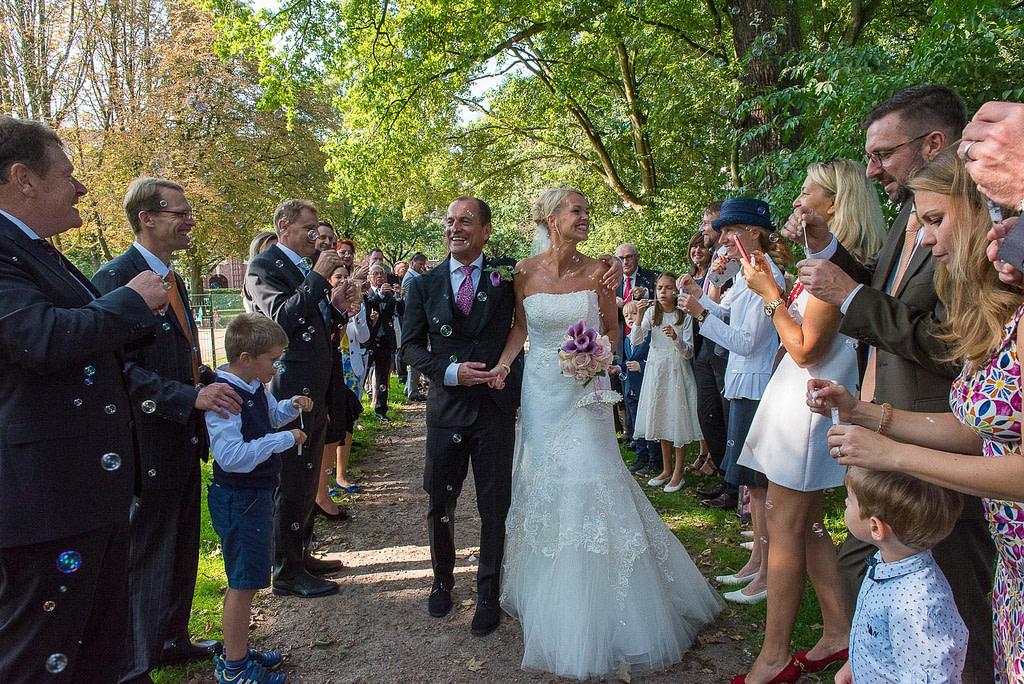 Das Hochzeitspaar läuft voller Freude an seinen Hochzeitsgästen vorbei, die spalier stehen und das Brautpaar in ein Meer aus Seifenblasen eindecken im Seelemannpark an der Eppendorfer Hochzeitskirche beim Hochzeitsfotograf Hamburg