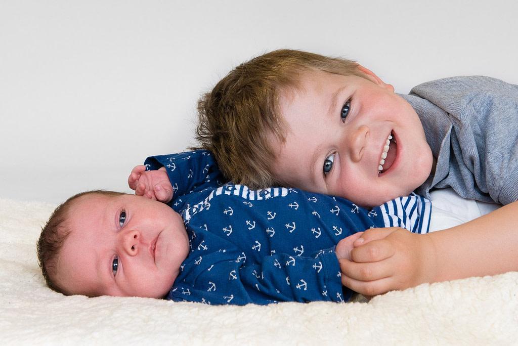 Geschwisterkind kuschelt sich an das Baby beim Baby Fotoshooting in Hamburg Blankenese