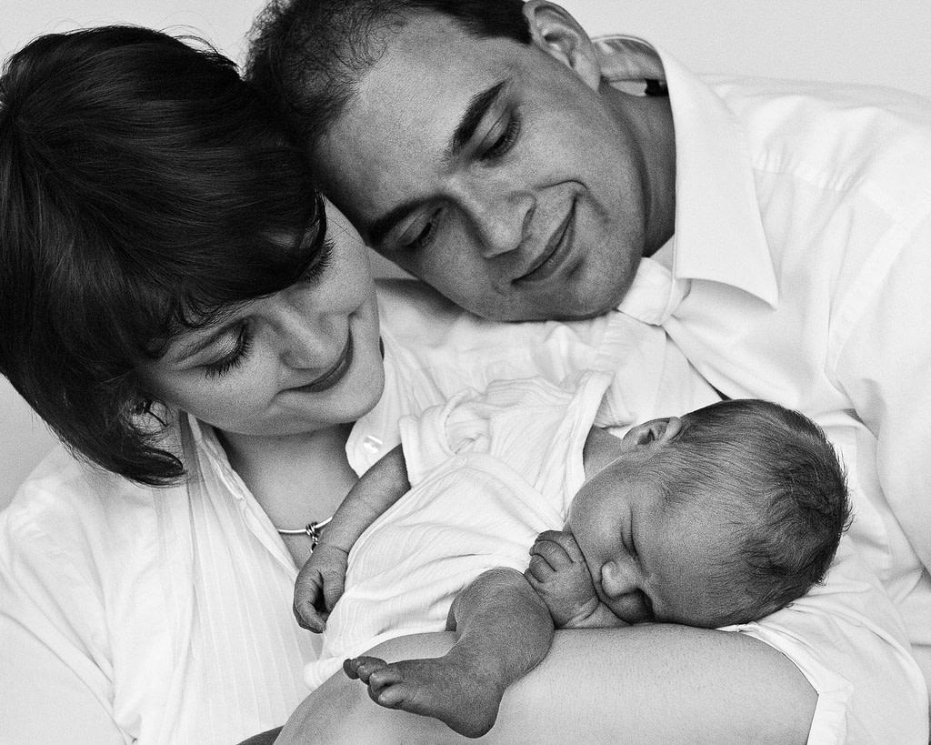 Mama und Papa halten ihr Baby im Arm und schauen es an bei der Neugeborenenfotografie in Hamburg Harburg
