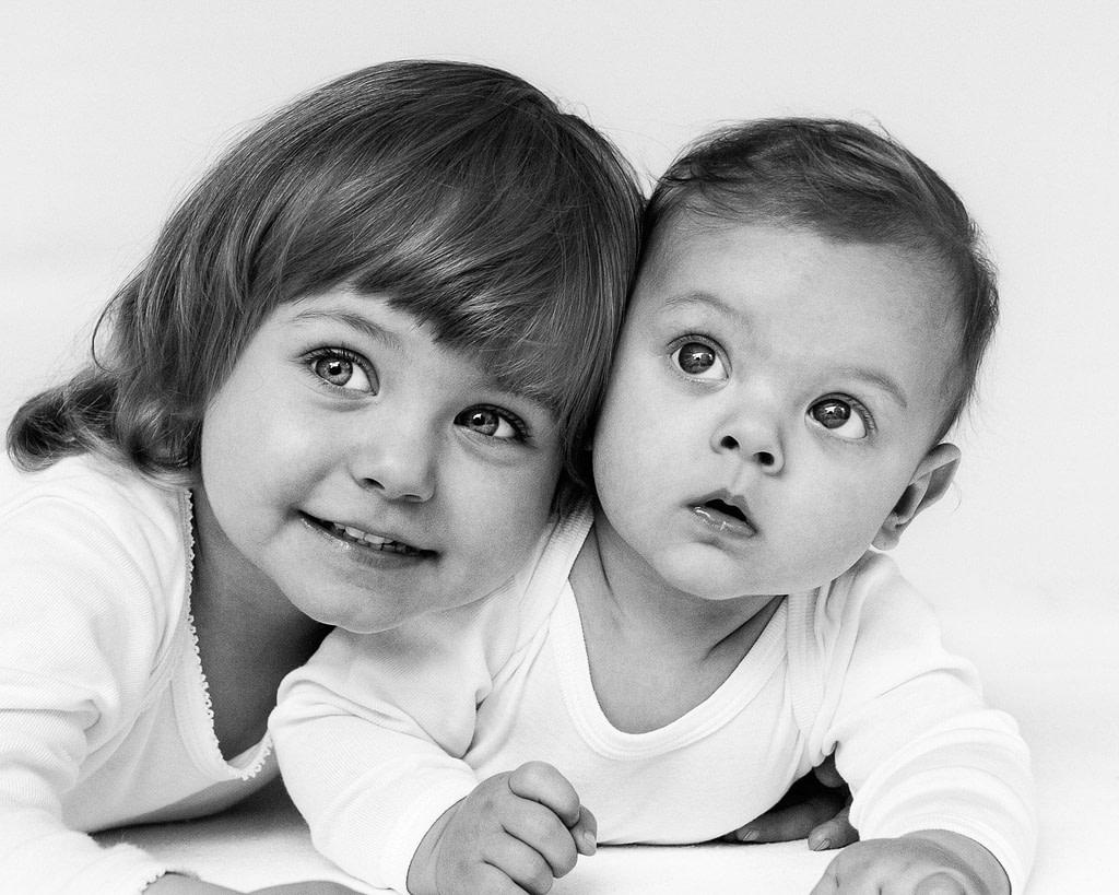 Kleine Schwester kuschelt sich an ihren kleinen Bruder bei der Kinderfotografie in Hamburg Poppenbüttel