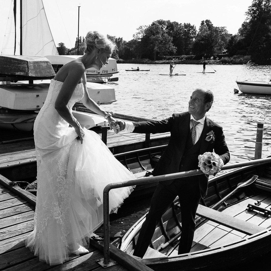 Der Bräutigam hilft seiner Braut in ein Ruderboot am Bobby Reich Bootsteg an der Außenalster in Harvestehude beim Hochzeitsfotograf Hamburg