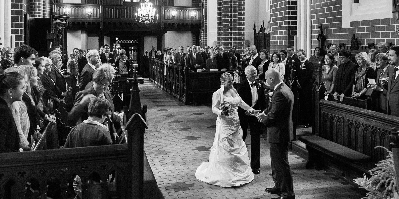 Brautvater übergibt die Braut dem Bräutigam vor der Trauung in der Sankt Marien Kirche in Röbel an der Müritz in Mecklenburg Vorpommern beim Hochzeitsfotograf Hamburg