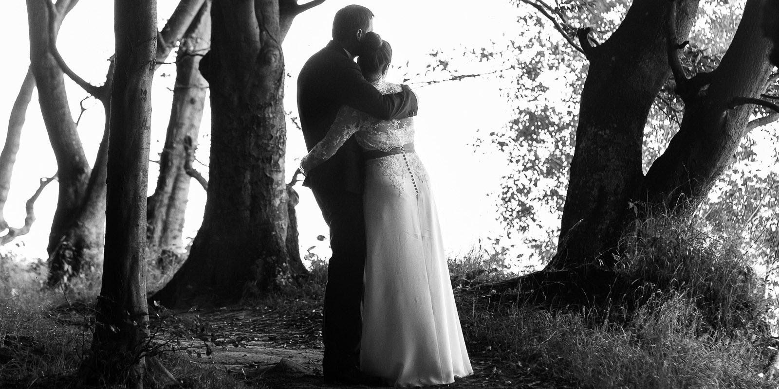 Verträumtes Hochzeitspaar wandelt durch den märchenhaften Hochuferwald am Weissenhäuser Strand an der Ostsee beim Hochzeitsfotograf Hamburg