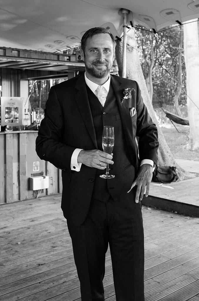 Glückseeliger Bräutigam beim Sektempfang im Bootshaus vom Schloß Weissenhaus Grand Village Resort am Weissenhäuser Strand an der Ostsee beim Hochzeitsfotograf Hamburg