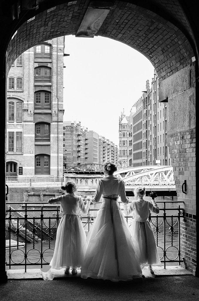 Die Braut mit ihren Blumenkindern am kleinen Fleet mit Blick auf den Wandrahmsfleet in der Hamburger Speicherstadt. Die Hochzeitsbilder vom Hochzeitsfotograf Hamburg