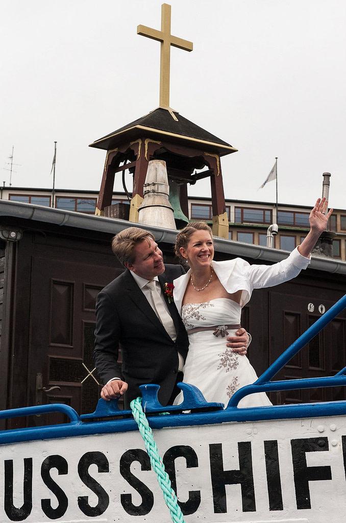 Das Hochzeitspaar winkt seinen Hochzeitsgästen von der Flußschifferkirche zu. Die Hochzeitsbilder vom Hochzeitsfotograf Hamburg