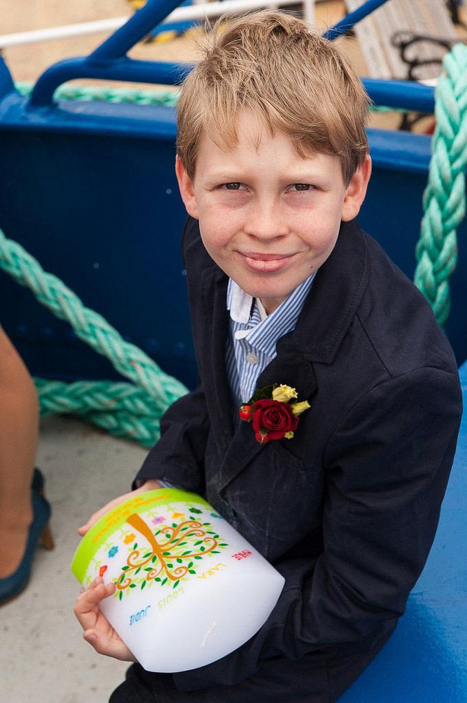 Der Sohn des Bräutigams hält die Taufkerze auf der Flußschifferkirche. Die Hochzeitsbilder vom Hochzeitsfotograf Hamburg