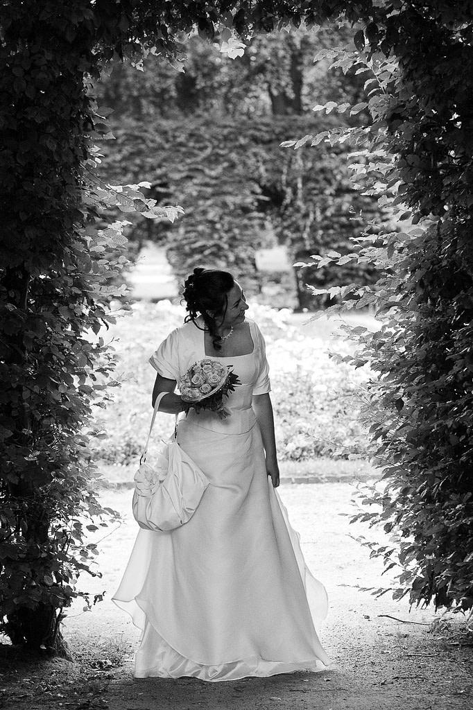 Die Braut hält Ausschau nach ihrem Bräutigam im Adam und Eva Heckengarten im Hamburger Stadtpark in Winterhude bei den Brautpaarfotos beim Hochzeitsfotograf Hamburg