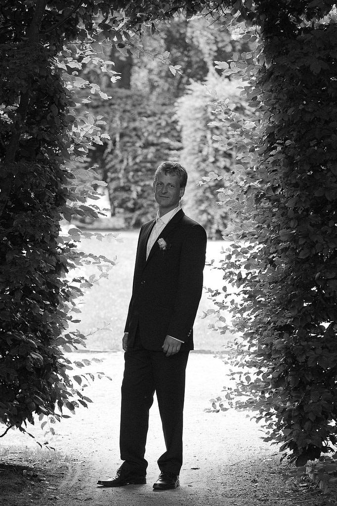 Der Bräutigam posiert für seine Braut im Adam und Eva Heckengarten im Hamburger Stadtpark in Winterhude bei den Brautpaarfotos beim Hochzeitsfotograf Hamburg