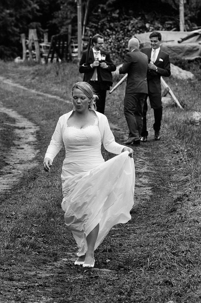 Hochzeitspaar mit Hochzeitsgästen bei der Landhochzeit läuft gemeinsam über die Felder am Gutshof Woldzegarten in Mecklenburg Vorpommern beim Hochzeitsfotograf Landhochzeit Hamburg
