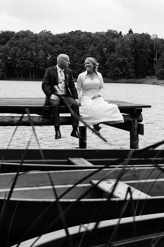 Hochzeitspaar sitzt händchenhaltend auf dem Bootssteg bei der Landhochzeit am Tangahnsee bei Warlow am Gutshof Woldzegarten in Mecklenburg Vorpommern beim Hochzeitsfotograf Landhochzeit Hamburg