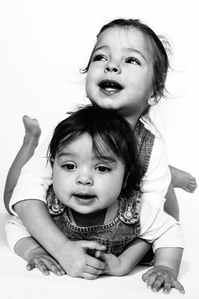 Baby und große kleine Schwester turnen gemeinsam auf der Tagesdecke beim Baby Fotoshooting zuhause in Hamburg Eppendorf