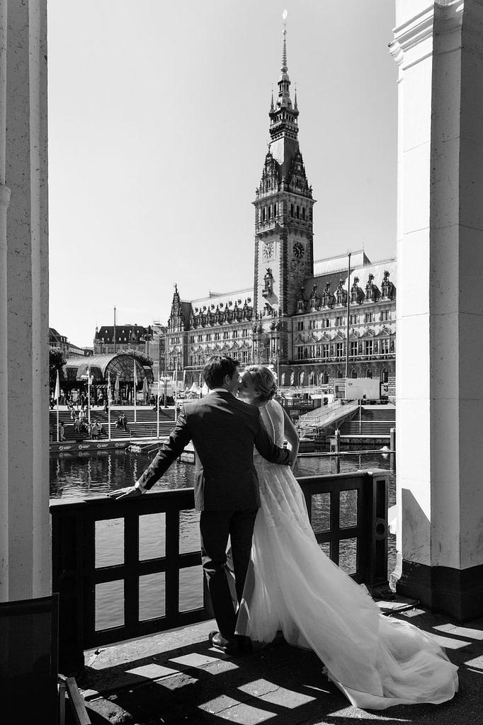 Hochzeitskuß an den Alsterarkaden mit Blick auf das Hamburger rathaus beim Hochzeitsfotograf Hamburg