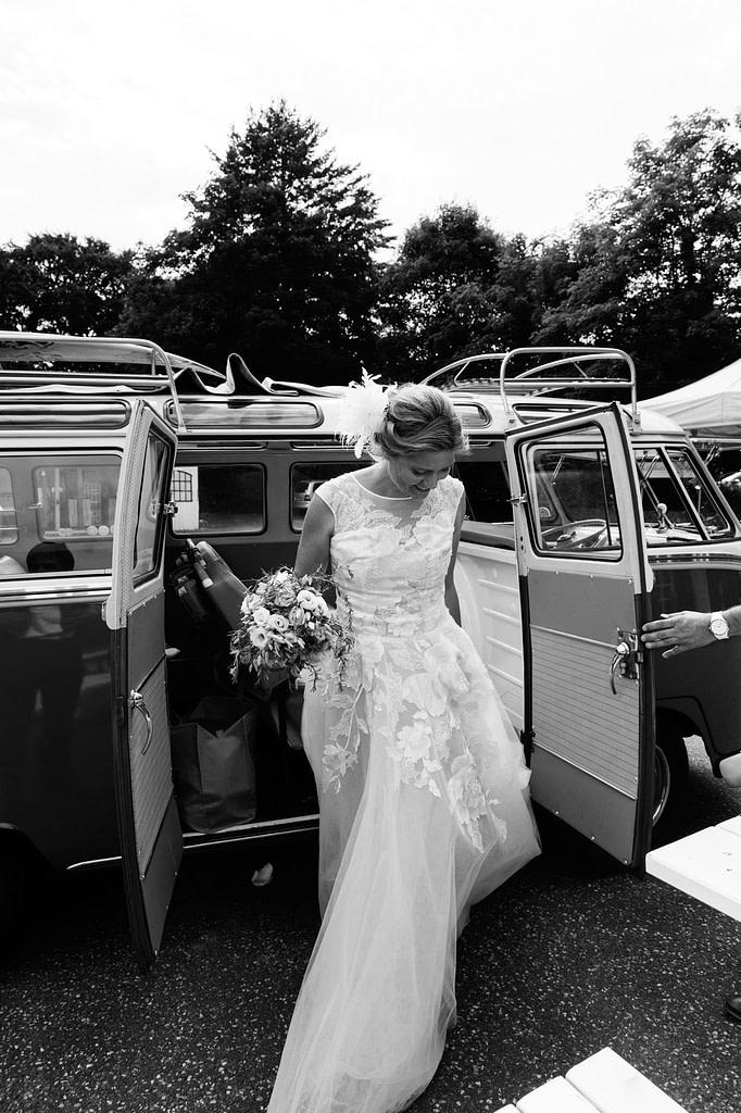 Die Braut steigt aus dem Hochzeitsauto VW Bus T1 am Goldschätzchen der Koch Fabrik auf dem Golf Park Peiner Hof in Priesdorf beim Hochzeitsfotograf Hamburg