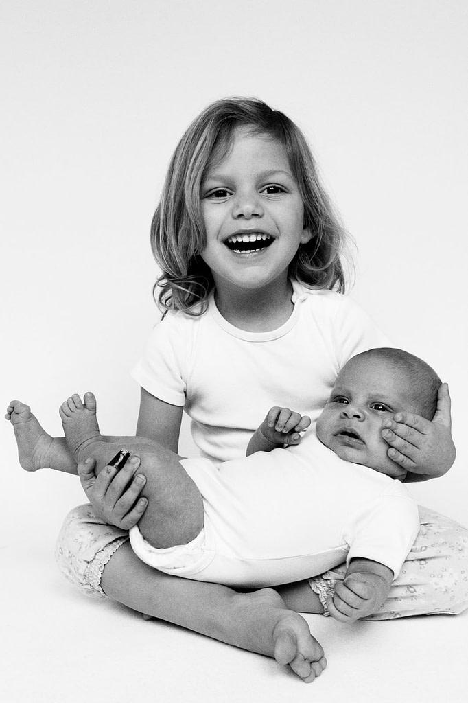 Baby und große kleine Schwester turnen gemeinsam auf der Tagesdecke beim Baby Fotoshooting zuhause in Hamburg Poppenbüttel