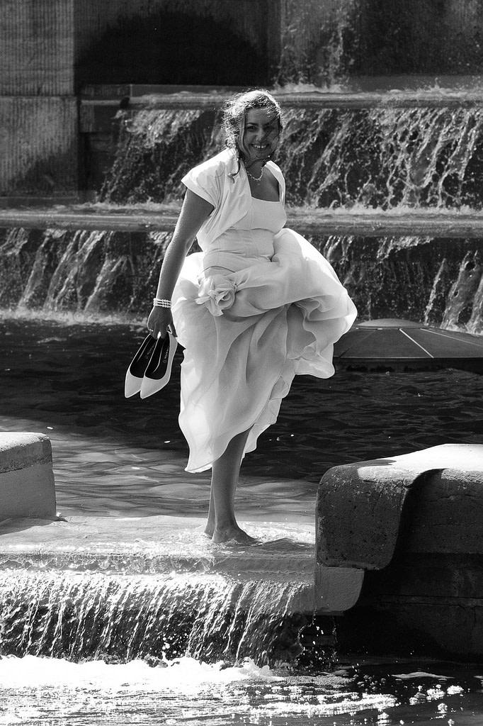 Braut im Brautkleid badet mit den Füssen im Springbrunnen vor dem Planetarium im Hamburger Stadtpark bei den Brautpaarfotos bei den Brautpaarfotos beim Hochzeitsfotograf Hamburg