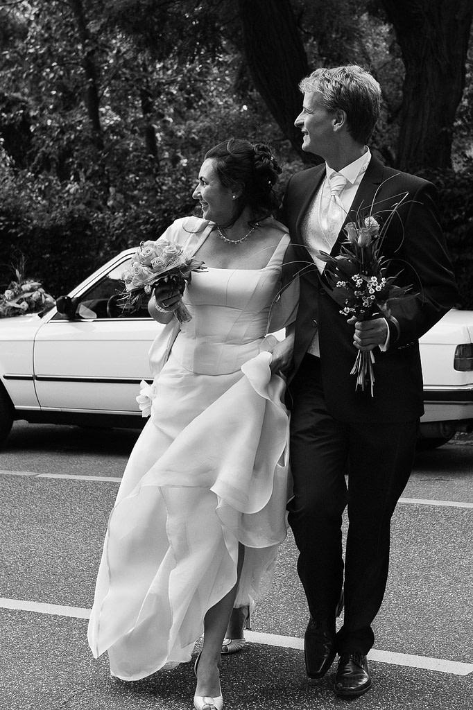 Hochzeitspaar überquert die Straße auf dem Weg zur Liebesinsel am Stadtparksee im Hamburger Stadtpark bei den Brautpaarfotos beim Hochzeitsfotograf Hamburg
