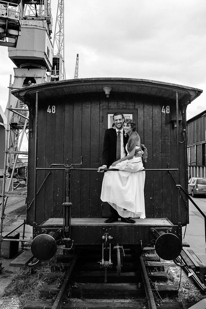 Hochzeitspaar im historischen Wagon auf den Kaianlagen des hafenmuseums HamburgHochzeitspaar schlendert über die Kaianlagen am Australiakai im Hamburger Hafen beim Hochzeitsshooting mit dem Hochzeitsfotograf Hamburg
