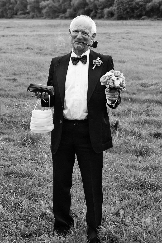 Brautvater hält den Brautstrauß der Braut bei den Hochzeitsfotos im Park vom Gutshof Woldzegarten in Mecklenburg Vorpommern beim Hochzeitsfotograf Landhochzeit Hamburg