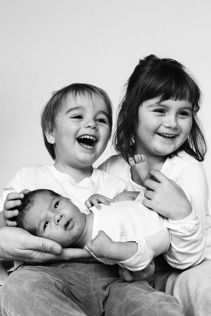 Geschwister kuscheln mit Baby beim Baby Foto Shooting in Hamburg