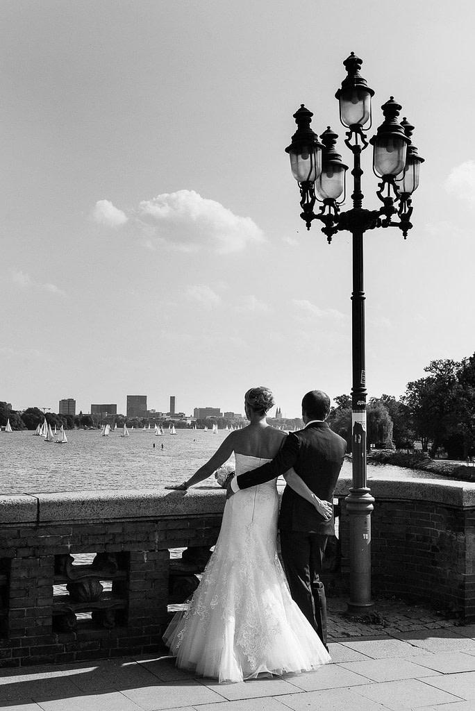 Braut umd Bräutigam Arm in Arm auf der Krugkoppelbrücke in Harvestehude mit Blick auf die Außenalster beim Hochzeitsfotograf Hamburg
