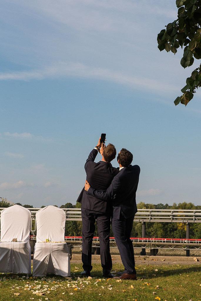 Bräutigam und Trauzeuge beim Selfie an der Villa im Jachthafen bei Hochzeitsfotografie Hamburg