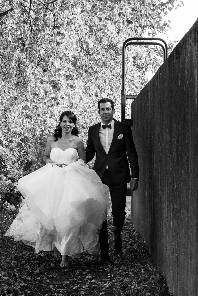 Das Hochzeitspaar läuft im Parkhafen die Flutschutzmauer entlang bei Hochzeitsfotografie Hamburg