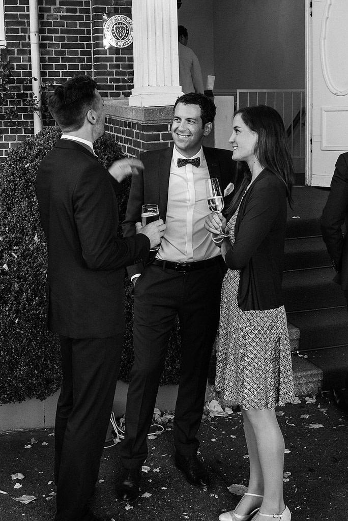 Bräutigam im Gespräch mit Hochzeitsgästen an der Villa im Jachthafen bei Hochzeitsfotografie Hamburg