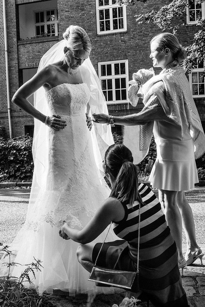 Letzte Korrekturen am Hochzeitskleid vor dem Einzug in die Eppendorfer Hochzeitskirche beim Hochzeitsfotograf Hamburg