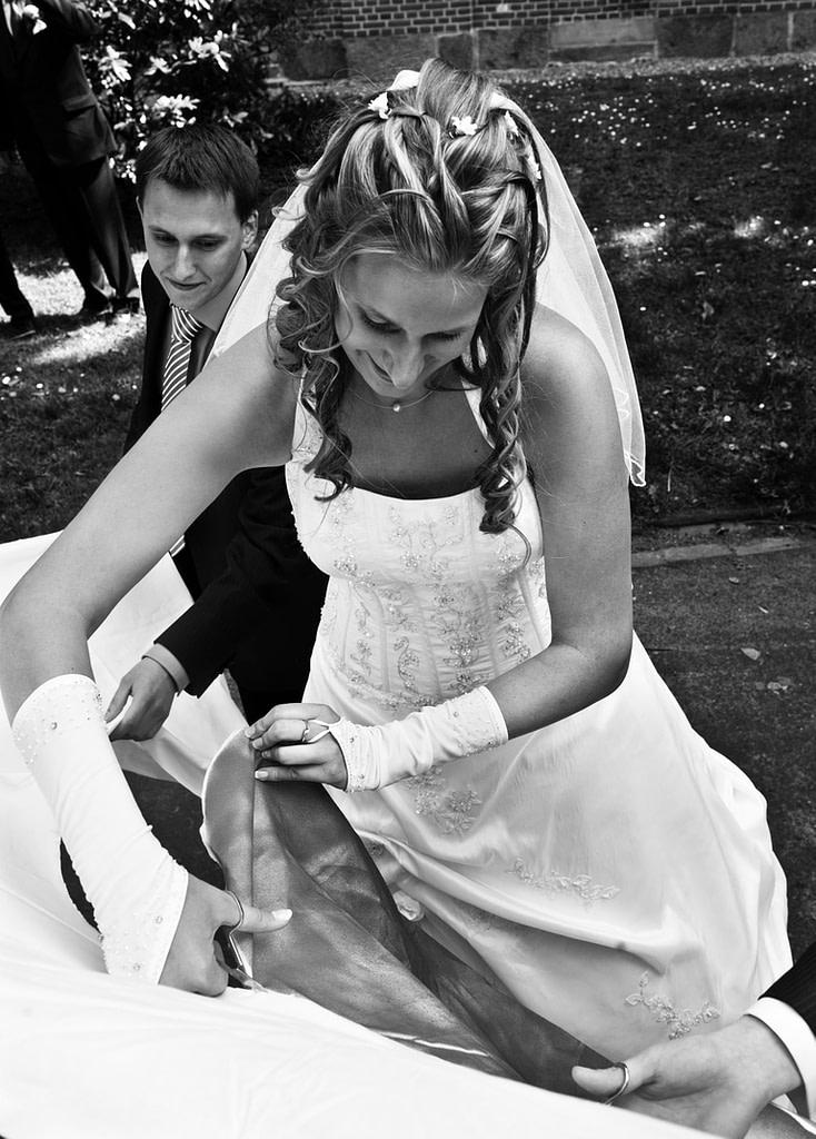 Hochzeitspaar beim Ausschneiden von einem Herz aus einem Bettlaken nach der Trauung vor der Kirche beim Hochzeitsfotograf Hamburg