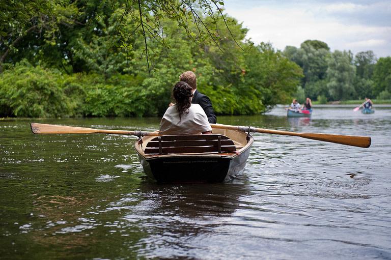 Hochzeitspaar im romantischen Ruderboot auf dem Stadtparksee in Hamburg Winterhude bei den Brautpaarfotos beim Hochzeitsfotograf Hamburg